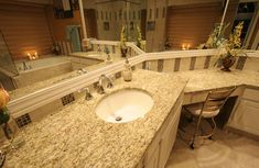 This designer bathroom sports a Giallo Ornamental granite counter top and a custom glass tile backsplash. The granite edge profile for this counter is full bullnose, for that high-end custom look..
