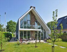 Een moderne woning die zich kenmerkt door zijn hoofdvorm en natuurlijke materialen die zijn toegepast.