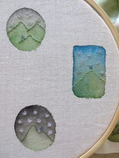 Anna Bradford paints little inchie splotches with watercolor-like fabric paint, irons on back to set, then doodles with stitches to make little landscapes...