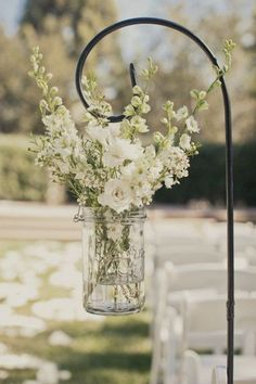 white flowers on mason jar wedding aisle decor / http://www.himisspuff.com/simple-elegant-all-white-wedding-color-ideas/10/