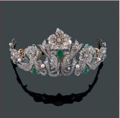 A diamond, natural pearl and emerald flora tiara, circa 1880, Spanish in origin. Featuring a tumult of diamond flower heads intertwined with diamond foliate scrolls; with pear-shaped emeralds and button pearls.