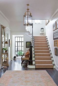 A large window at one end of this entry hall opens the space and floods it with gorgeous, natural light - Traditional Home®, seagrass stair runner:
