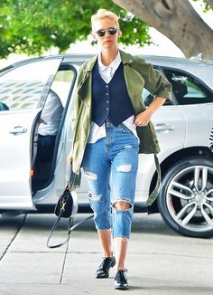January Jones wears a button-down shirt layered with a navy blue vest, army jacket, cropped distressed jeans,, round sunglasses, and black oxfords