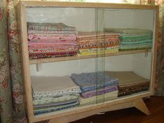 Fabulous use of a vintage glass front display cabinet to store fabric!