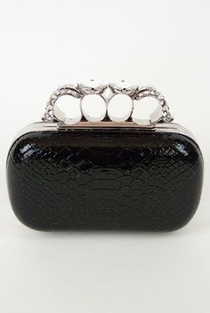 Long, rectangular faux snakeskin clutch in black with gold speck features 4 finger knuckle handle skull knuckles with clear stones.  Comes with removable silver chain to wear as a shoulder clutch.  $49.00