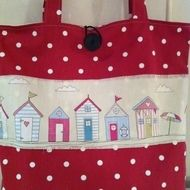 These great little beach huts will brighten up and shopping trip. Ideal for the beach as well. Beach huts in pastel shades and the main body of the bag in a Claret red spotty fabric. Good quality cotton fabric. Details on both sides. Large double pocke...