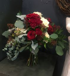 Stunning Bridal bouquet with white avalanche roses, naomi roses, red spray roses, soft rosques, viburnum berries, eucalyptus, silver leaves.
