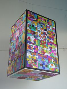 Le pavé expose 123 œuvres d'élèves de 6eme : compositions rectangulaires aux proportions du nombre d'Or, utilisant la symétrie axiale. Sur sa base inférieure : un pavage de carrés spiralés.