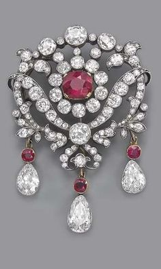 AN ANTIQUE RUBY AND DIAMOND BROOCH. The central cushion-shaped ruby and old-cut diamond cluster to the openwork diamond floral surround, suspending three detachable pear-shaped diamond and ruby drops, mounted in silver and gold, circa 1880.
