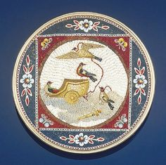 An early 19th century Italian micromosaic brooch Of circular shape depicting a chariot in cloud with four birds and a torch within a red square border with butterfly detail to a blue surround with floral decoration, with mother of pearl reverse, circa 1820