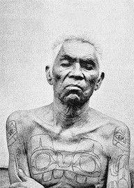 Haida Chief Xana showing his chest and arm tattoos