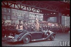 Adolf Hitler cruises past his SS Honor Guard in his open-air Mercedes-Benz as he greets the cheering masses of German citizens in attendance to view the military parade.
