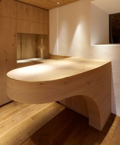 Rounded oak counter with integrated brass ornament and curved base.