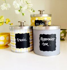 Upcycling Tin Cans with Scrapbooking paper, chalkboard labels and little bit of spray varnish.  Easy to make and great containers for the kitchen or office.