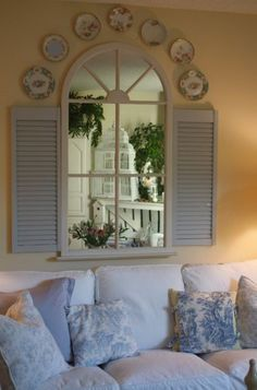 "Create a ""window"" by recyling a mirror and shutters."