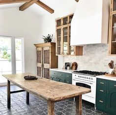 15 Farmhouse Style Decor Ideas to Get You Started Love this reclaimed wood kitchen island table. Green kitchen cabinets, wood beam ceiling, and gray tile kitchen floor. Grey Kitchen Tiles, Green Kitchen Cabinets, Kitchen Island Table, Kitchen Flooring, Dark Cabinets, Green Kitchen Island, Kitchen Black, Kitchen Backsplash, Glass Cabinets