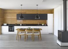 Modřín byl použitý i na obklad stěny v kuchyni, velký jídelní stůl a židle Merano (TON) odpovídají tvarově čistému interiéru.