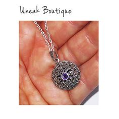 Round Amethyst Marcasite Locket. This pretty marcasite locket is set with a deep purple Siberian Amethyst in the centre of the locket which is surrounded by an intricate mix of openwork swirl shapes, delicate silver beading and etching all set with gleaming marcasite gems.  A stunning dainty marcasite locket design with a vintage quality which is perfect for a keepsake gift which can be passed down through the family in years to come.