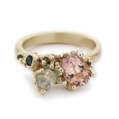 A statement asymmetrical cocktail ring from Ruth Tomlinson featuring tourmaline, aquamarine and topaz in yellow gold, handmade in her central London studio.