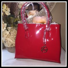 "PATENT LEATHER TOTE IN RADICAL RED Solid open top, with magnetic snap closure.  Textured faux leather, for our animal conscious friends. Side snap buttons for expansion, if desired. Inside soft felt like lining with button flap and zippered pocket enclosures.  Handles are 24"" from side to side. A true Lady's bag, for a fraction of the cost of designer.  Dustcover included.  Also available in BLACK and IVORY A must have look that can be carried all seasons, and never goes out of style. 15W X…"