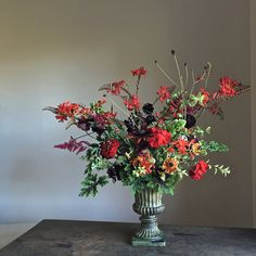 An arrangement of reds and greens—complementary colours—showing a range of reds: oranges, crimsons, scarlets, burgundies and plums. Plants include Crocosmia 'Lucifer', Pelargonium quercifolium 'Chocolate-Mint', Scabiosa atropurpurea 'Black Knight', Geranium, Astilbe, Molucella, Sanguisorba, Pittosporum 'James Stirling', Helenium, Echibeckia, sweet peas and Zinnia 'State Fair'.