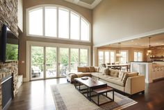 Open living space with 2 story stone fireplace and a ton of natural lighting