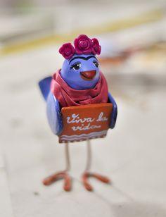 Vibrante, apaixonada e intensa. A passarinha Frida, gosta da vida e da arte. <br>Viva la vida! <br> <br>Exclusivo objeto decorativo feito de papel machê. <br> <br>Dimensões do produto: <br>8 cm de comprimento <br>11,5 cm de altura <br>5 cm de largura