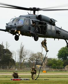 A 56th Rescue Squadron pararescue team deploys with equipment from a Sikorsky HH-60G Pave Hawk during a combat search and rescue exercise at Royal Air Force Lakenheath, England, April 17, 2014. The rescue mission scenario included pararescue and security forces teams recovering a victim injured by an improvised explosive device. (U.S. Air Force photo by Staff Sgt. Emerson Nuñez/Released)