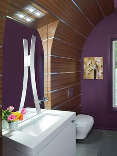 In this contemporary bathroom, a curved wooden front covers an existing wall. The curved structure creates a recess and makes room for a flat surface to mount a mirror and a faucet.