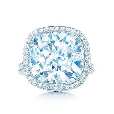 Cushion-cut diamond ring in platinum with round brilliant diamonds.