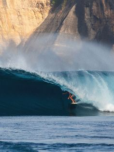 Tube.  You don't see that very often, a surfer catching a wave with a huge stone wall behind!