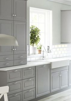 Grey cabinets, white subway tiles, white countertops