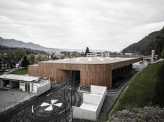 The waste materials collection centre is located in the middle of the City of Feldkirch. The aesthetic building made of wood from local forests makes the process of waste separation visible in the town, treating it wi. Feldkirch, Wooden Facade, Recycling Process, Timber Buildings, Recycling Center, Container Architecture, Roof Light, Outdoor Furniture Sets, Outdoor Decor
