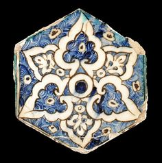 At auction September 2011. Origin, Egypt or Syria.  A hexagonal tile painted in underglazed cobalt blue and turquoise. The central circle is contained by overlapping palmettes outlined in black on a ground of blue scales with small floral devices.. Three of the palmettes alternatingly have smaller palmettes in their centre against blue scale grounds while the remaining three have a small central floral device also against a blue scale ground. Two thin parallel brown lines and a turquoise…