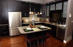 Dark, contemporary cabinetry;  Tile back-splash in horizontal pattern;  Pendant lights over granite counter;