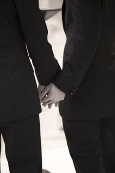 Bridegrooms in gay wedding holding hands
