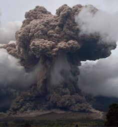 Explosive eruption of Indonesia's Sinabung volcano ejecting ash and gas high up into the atmosphere and pyroclastic flows sweeping down downslope