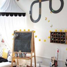 Myshörnan i barnens rum med bokhylla på väggen.