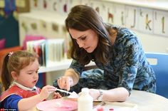 Kate lent a hand by holding a piece of paper while a youngster applied glue during an arts...
