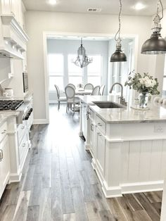 I'm obsessed with this white kitchen! The pendant lights and wood tile floor makes for a really gorgeous room!