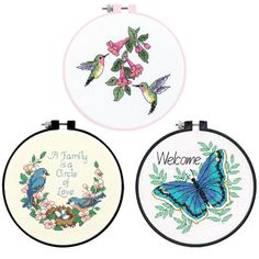 """SAVE when you buy the Flying Friends Bundle, a set of 3 designs in counted cross stitch! Perfect for kids and beginners of all ages. Counted cross stitch kits contain presorted cotton thread, 14 count cotton Aida, plastic hoop for stitching and finishing, needle, and easy instructions. Finished Size: 6"""" Diameter (15 cm). Top: Hummingbird Duo / Bottom Left: Family Love / Bottom Right: Welcome Butterfly."""