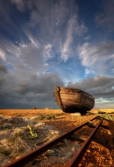 Boat on dry land and railroad track