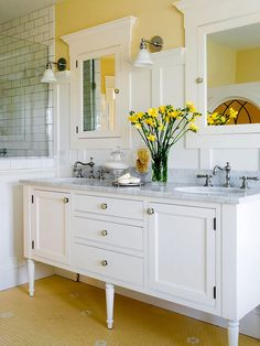 White + Butter Yellow A color palette of warm yellow and crisp white creates a vintage vibe in this master bathroom. White-painted paneling covers three-fourths of the bathroom's walls, while the upper portion features a sunny yellow hue. The thick, dark grout lines throughout the shower and floor tiling, plus the vanity's furniture-style construction, emphasize the bathroom's vintage aesthetic.