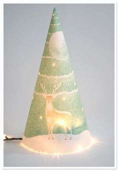 "I could make that! Just get a pretty, thin, Christmas-y patterned paper, punch some holes in it randomly, roll it into a cone shape, tape it together, and place over white Christmas lights. Could make several small ones and create a little Christmas ""forest"". Would be really cute as a table centerpiece!! I'm so doing this!!"