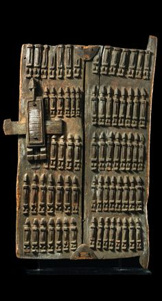 Africa | Granary door from the Dogon people of Mali | Wood, slightly encrusted brown patina, remains of kaolin, consisting of two wooden planks, joined by metal clamps