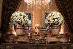 Mesa de doces clássica e elegante. Arranjos brancos, travessas em prata.  Foto: Braulio Delai