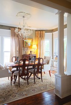 pleated drapery panels...love everything about this dining room...architecture, paneled window frames, hardwood flooring, lots of windows, arm chairs, traditional decor and that chandelier!!!