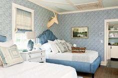 Husband-and-wife fabric designers Peter Fasano and Elizabeth Hamilton created the feminine palette for this guest bedroom. The cool colors, pretty paisley wallpaper and tufted headboard bring classic appeal to the space.