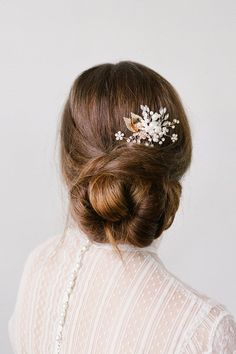 This versatile and delicate-looking floral hair comb consists of tiny pearl clusters, gold wiring, and gilded metal leaves. It is also available in silver.