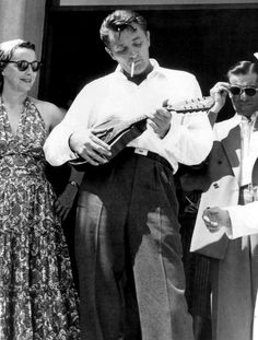 Robert Mitchum playing a mandolin while exiting a hotel in in France, 1954.
